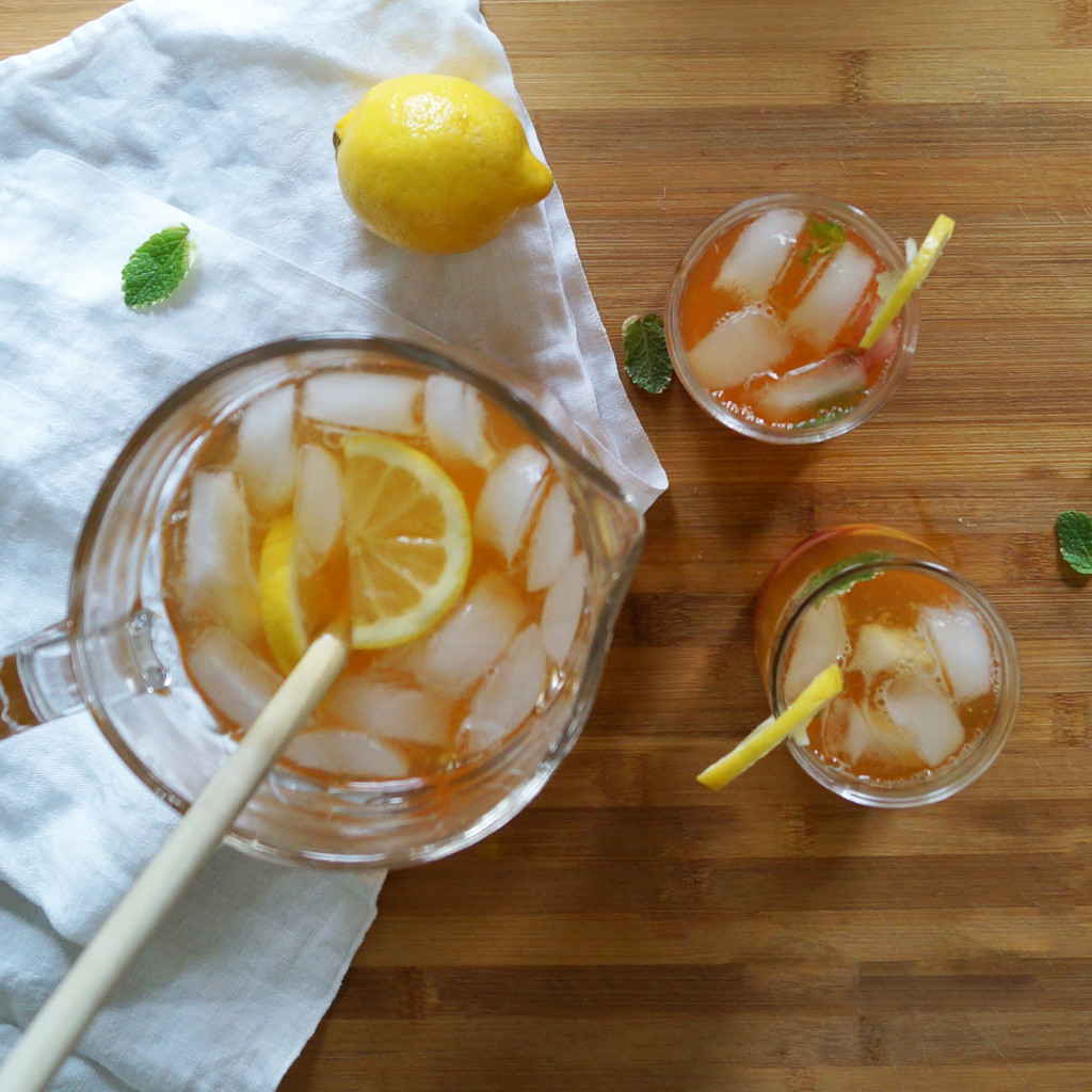 Glasses filled to the brim with ice and boozy Arnold palmer, garnished with mint leaves and lemon slices.