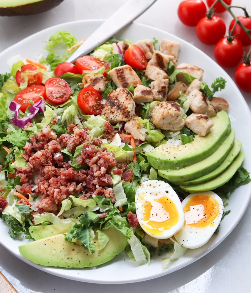A plated Taylor Farms Salad with grilled chicken, bacon, avocado and soft boiled eggs.
