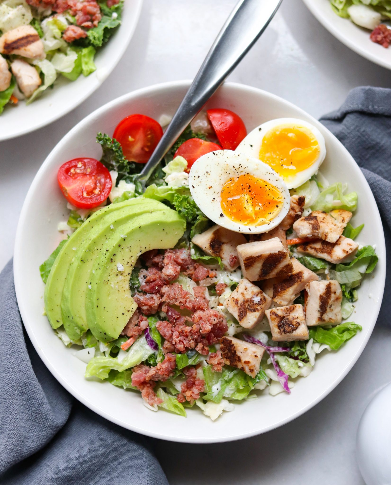 A completed dish with Taylor farms salad kit and added soft boiled eggs, tomatoes and avocado