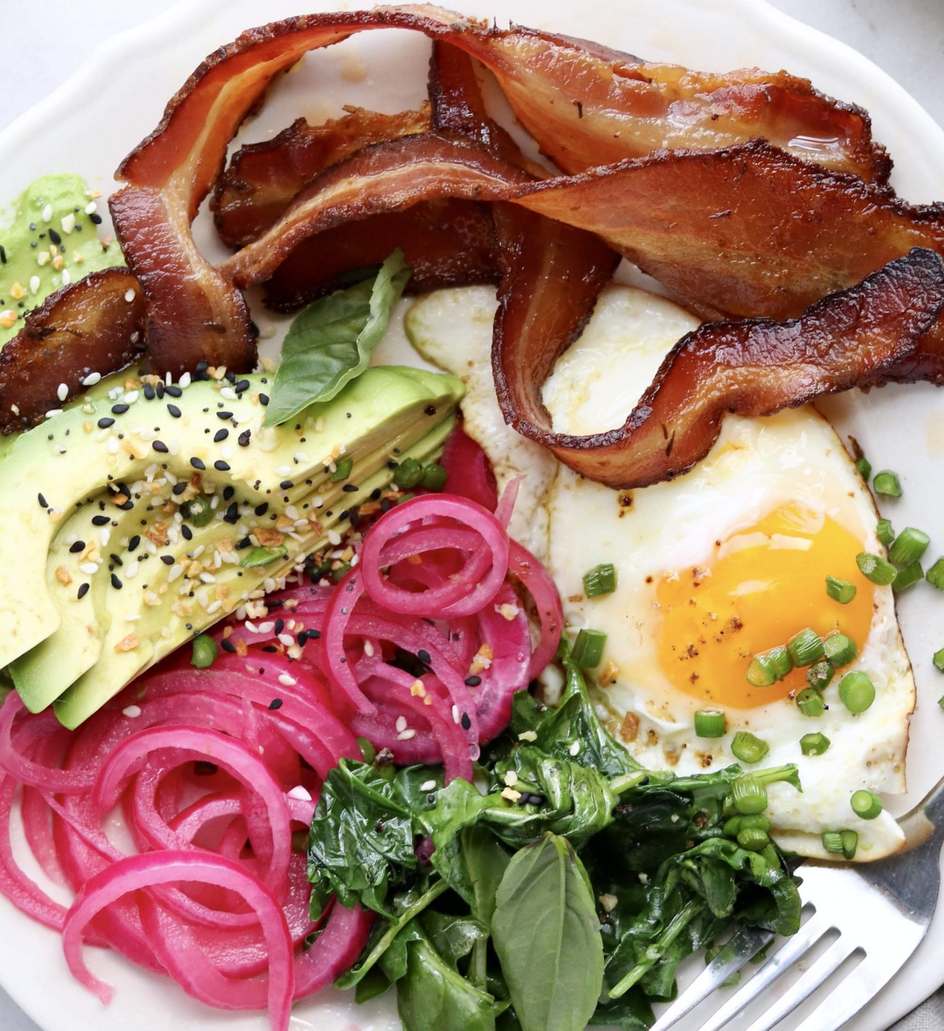 A completed dish of pickled onions, bacon, a fried egg, avocado and herbs.