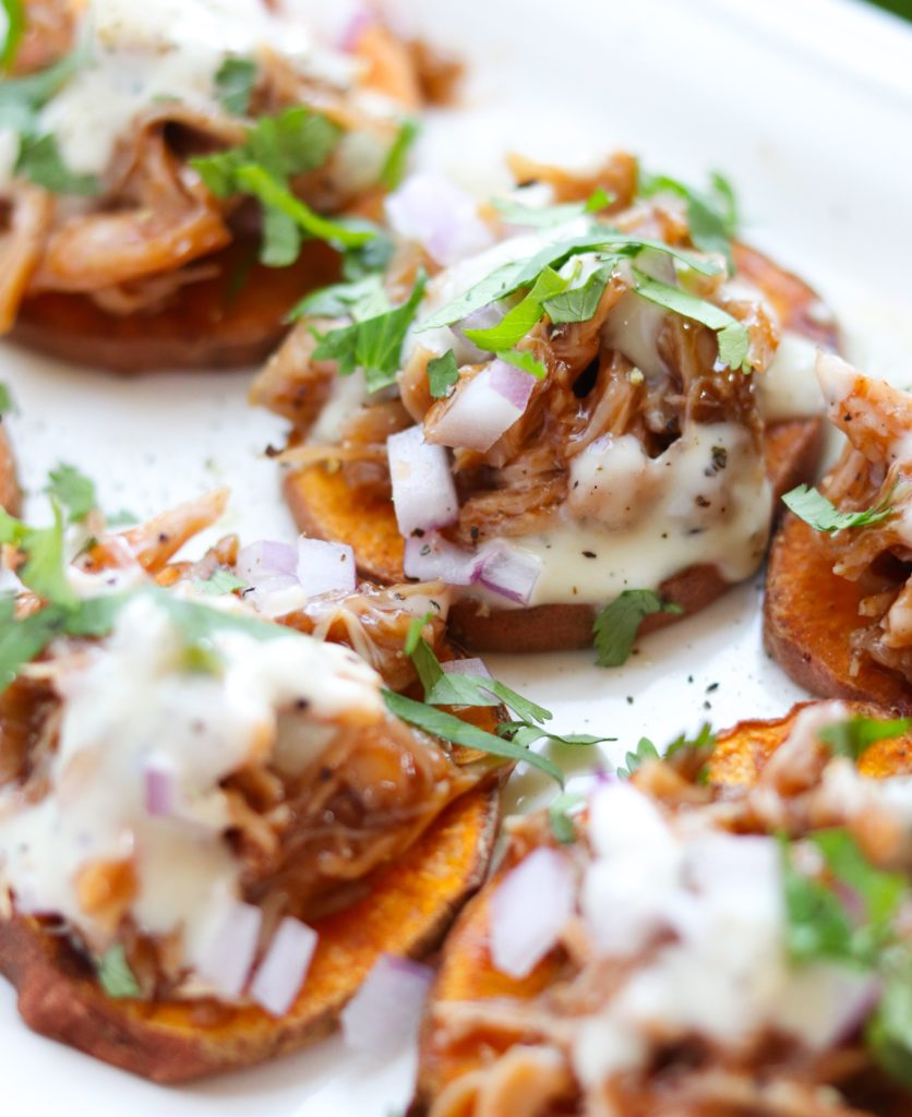Delicious Whole30 compliant roasted sweet potato rounds topped with bbq chicken, red onion, ranch, and cilantro. A really simple, crowd-pleasing  Paleo appetizer!