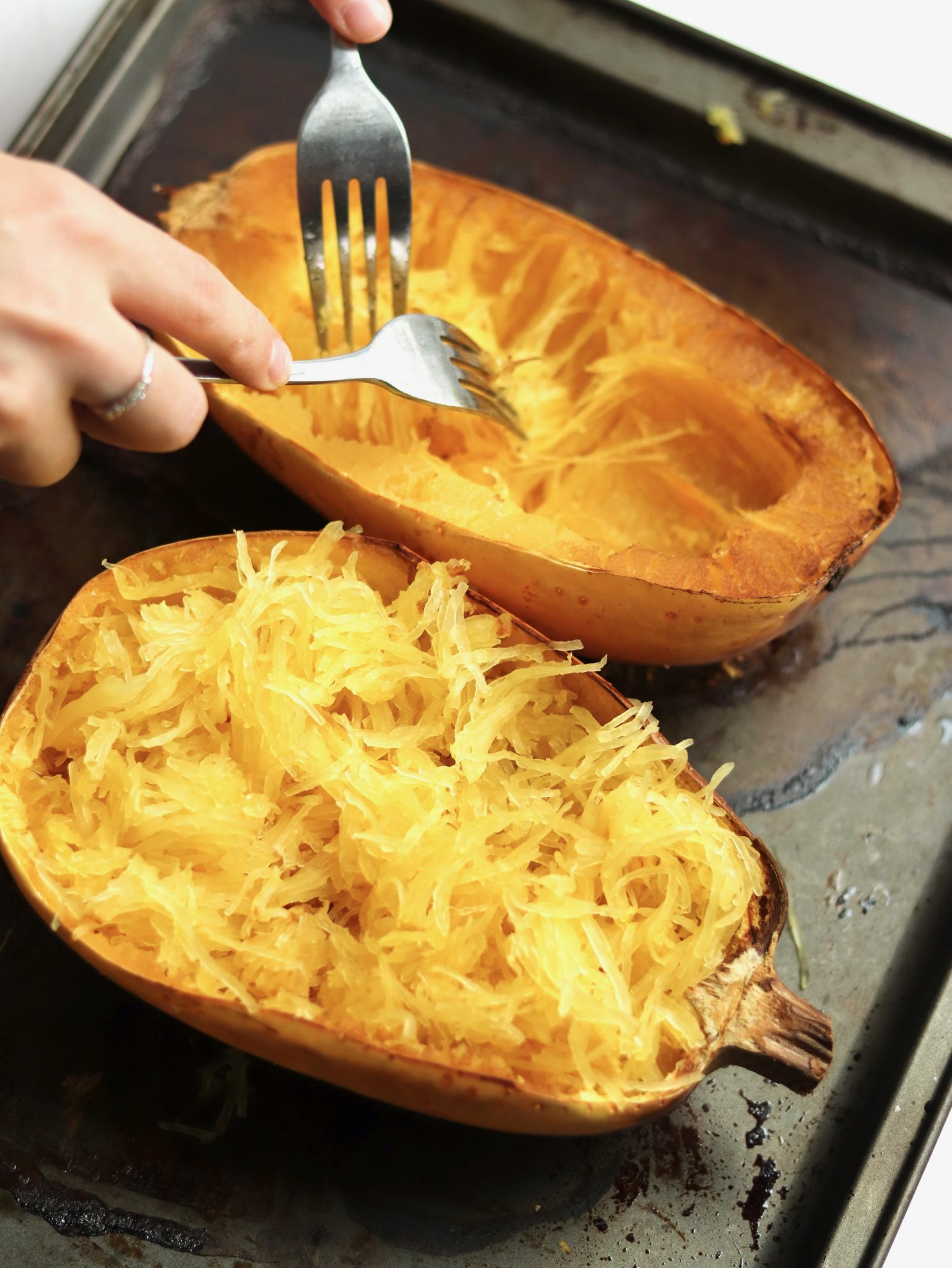 Use two forks to gently pull the cooked spaghetti squash flesh from the hard shells on a baking sheet.