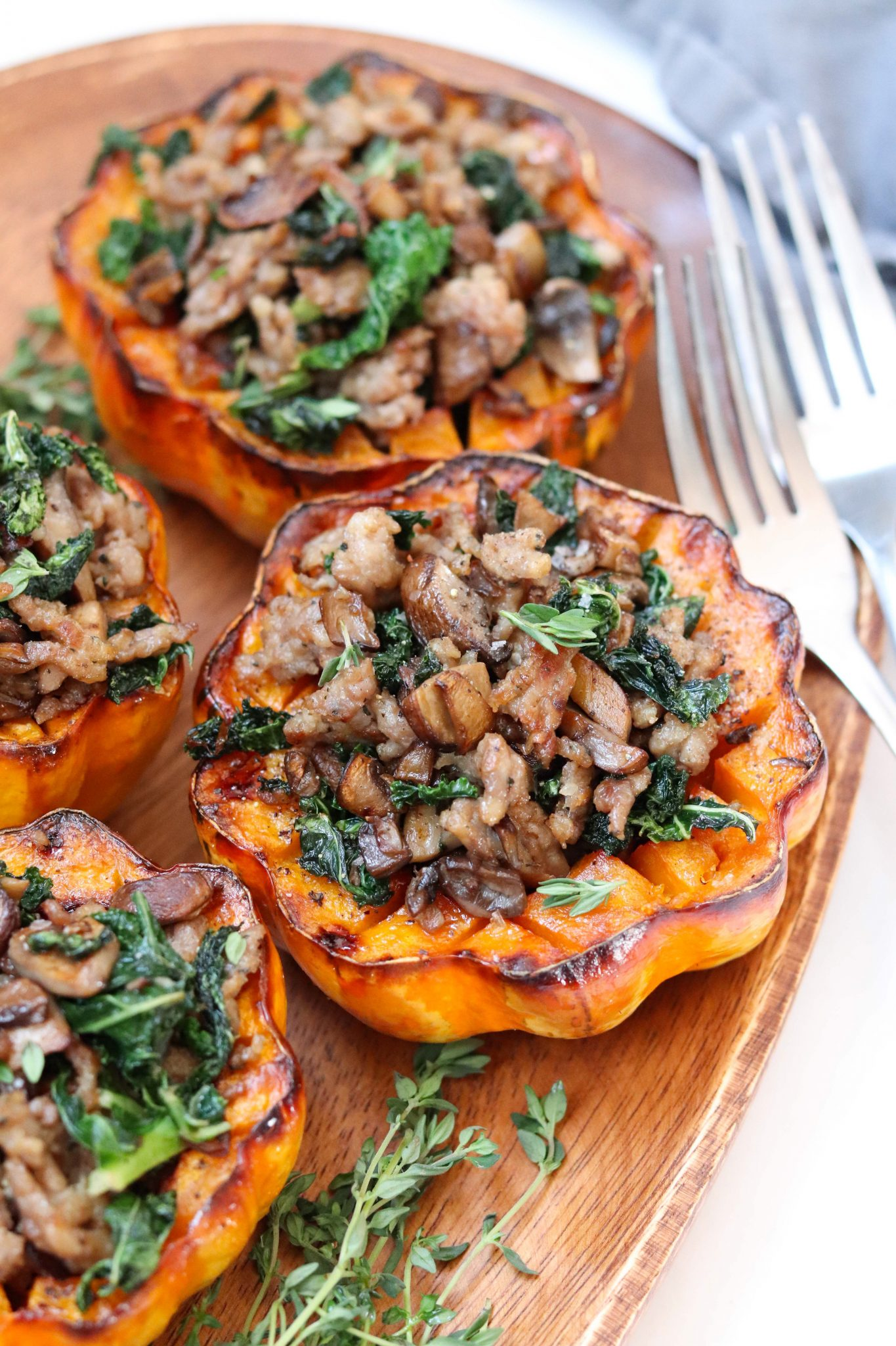 An absolutely delicious fall Whole30 dinner - Acorn Squash is roasted and stuffed with sausage and sautéd mushrooms and kale.