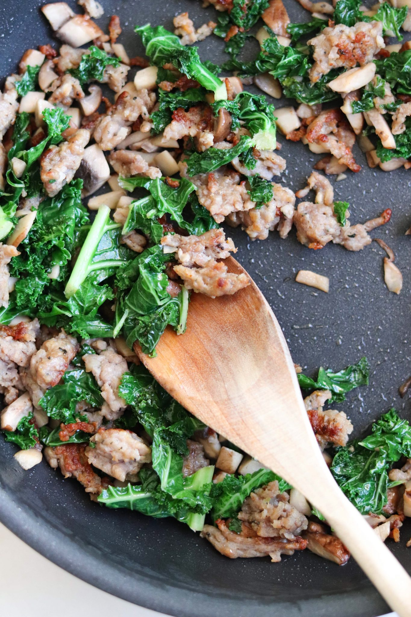 An easy Whole30 dinner - A skillet of sautéed mushrooms and kale mixed with savory sausage is ready to be stuffed into roasted acorn squash.