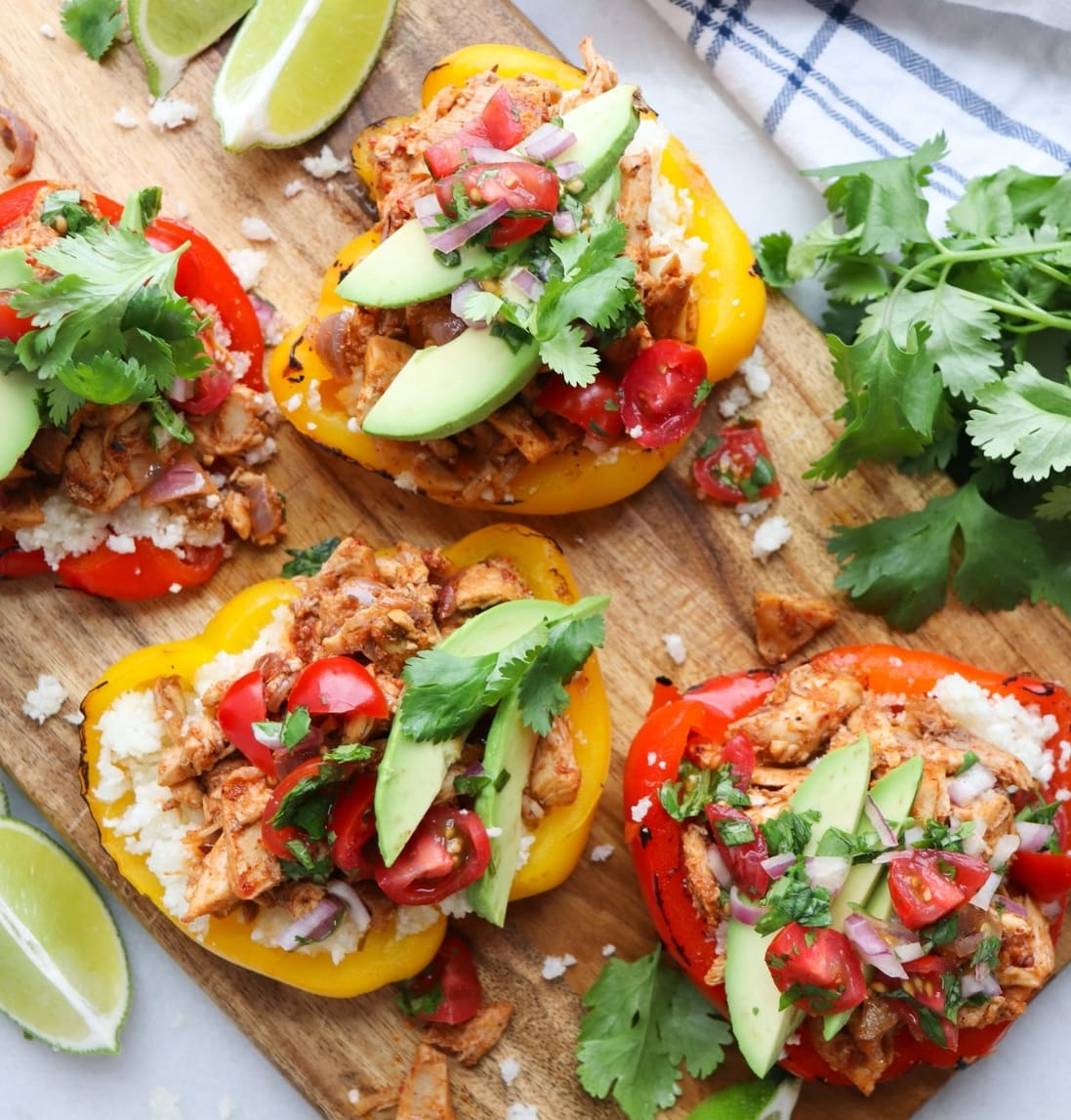 Whole30 Chicken Fajita Stuffed Peppers topped with fresh pico and avocado slices, finished dish
