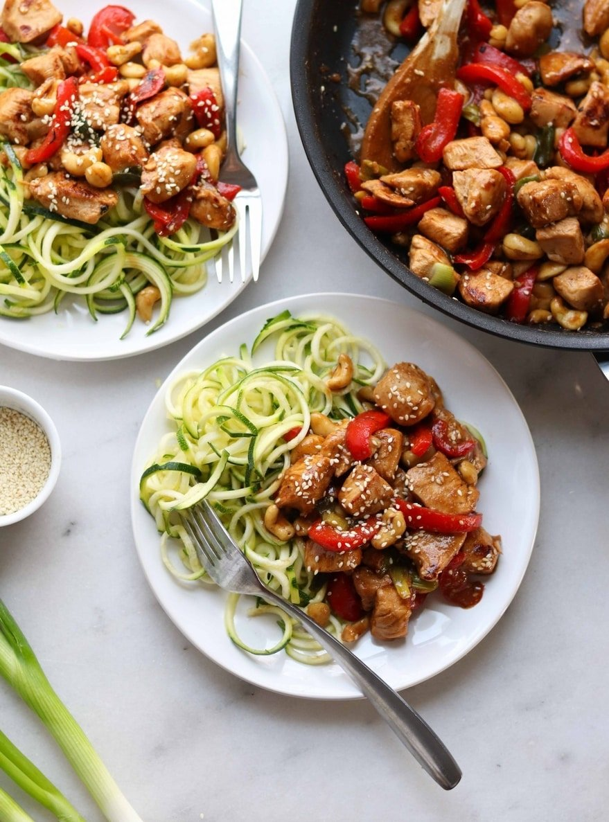Two white plates with spiralized zucchini noodles and a serving of Kung Pao Chicken.