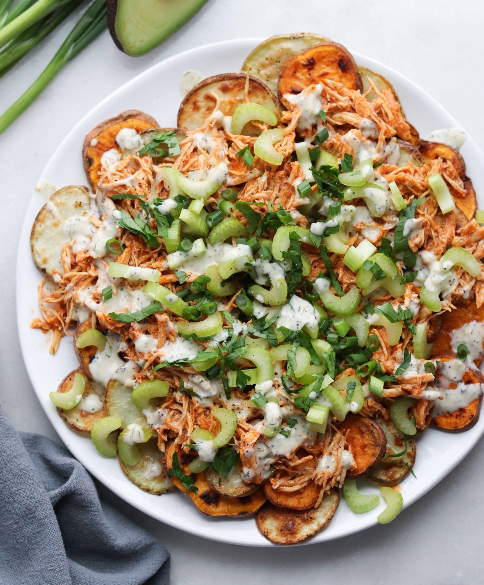 Paleo Buffalo Chicken is made in the Instant Pot and served over roasted potato rounds, then topped with celery, herbs, and ranch.