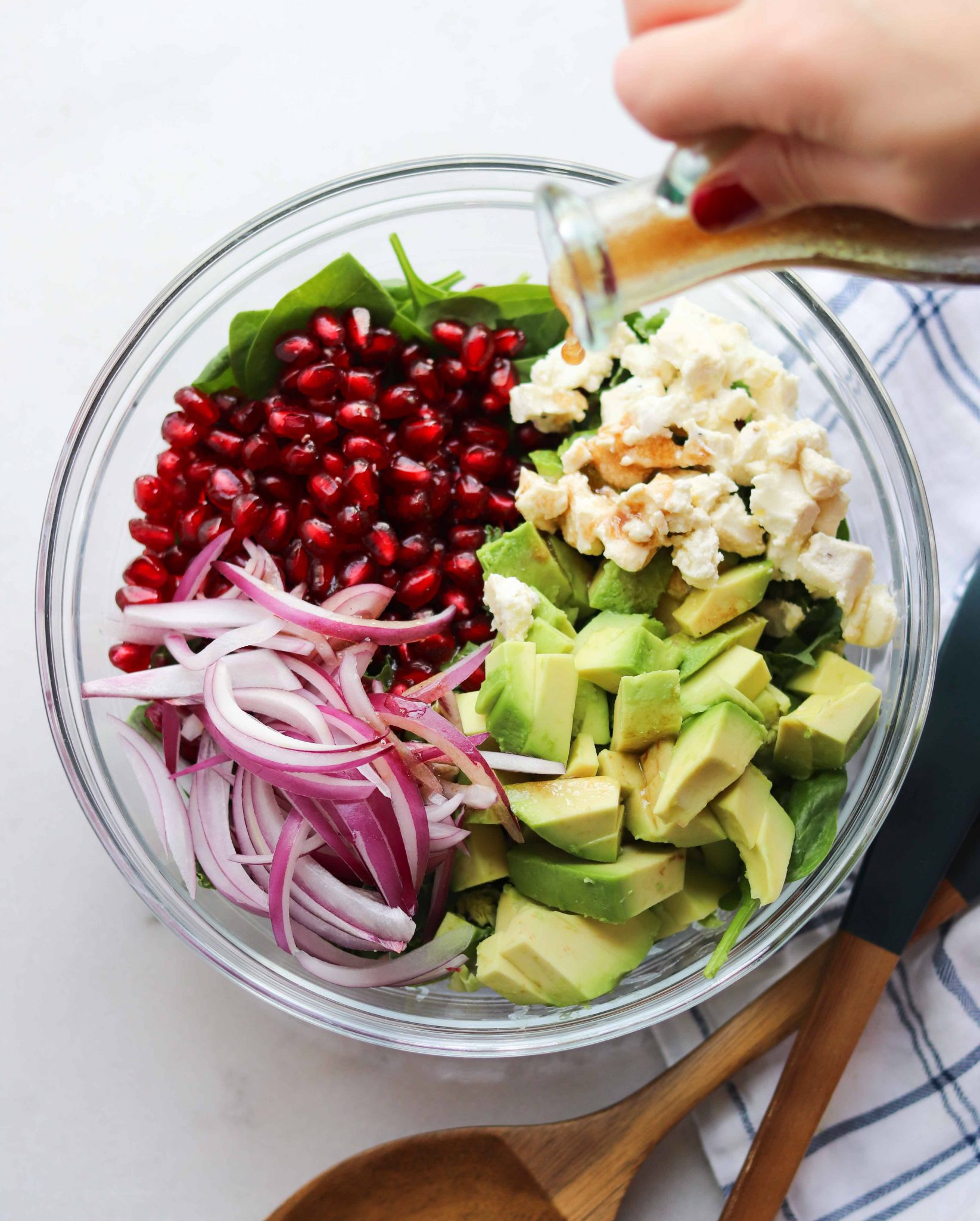 Pomegranate and Avocado Winter Salad in a glass bowl with a hand pouring the balsamic vinaigrette on top