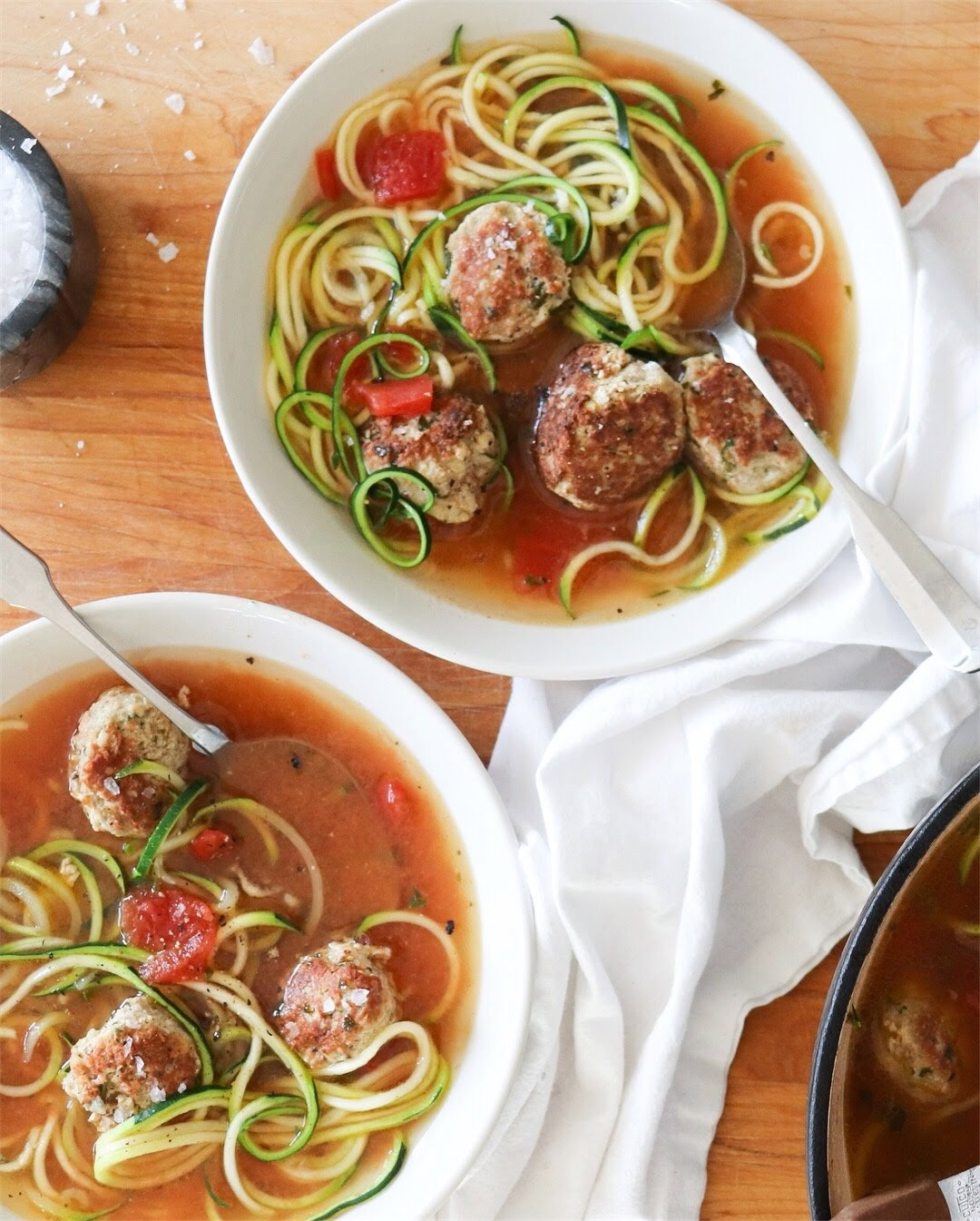 Two white bowls filled with turkey meatball and zucchini noodle soup.