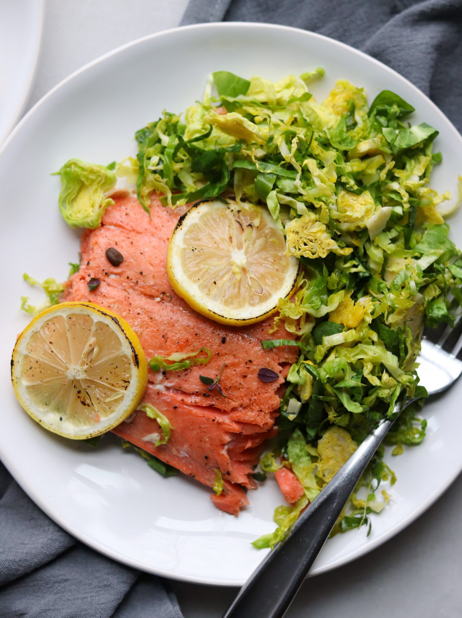 Roasted Salmon is set on a white plate with slices of lemon. The Brussels sprouts salad is on the side. Finished Dish, Plated