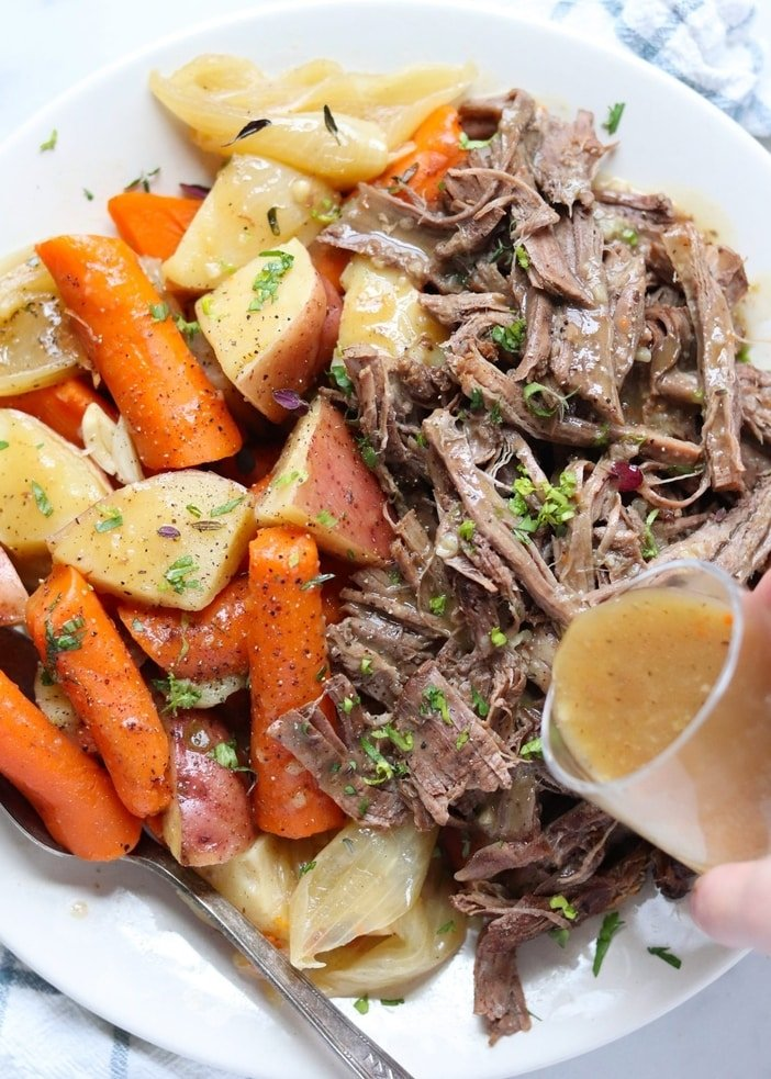The finished pot roast is plated on a large white plate beside the cooked carrots and potatoes. A hand is holding a glass cup, pouring gravy on top.