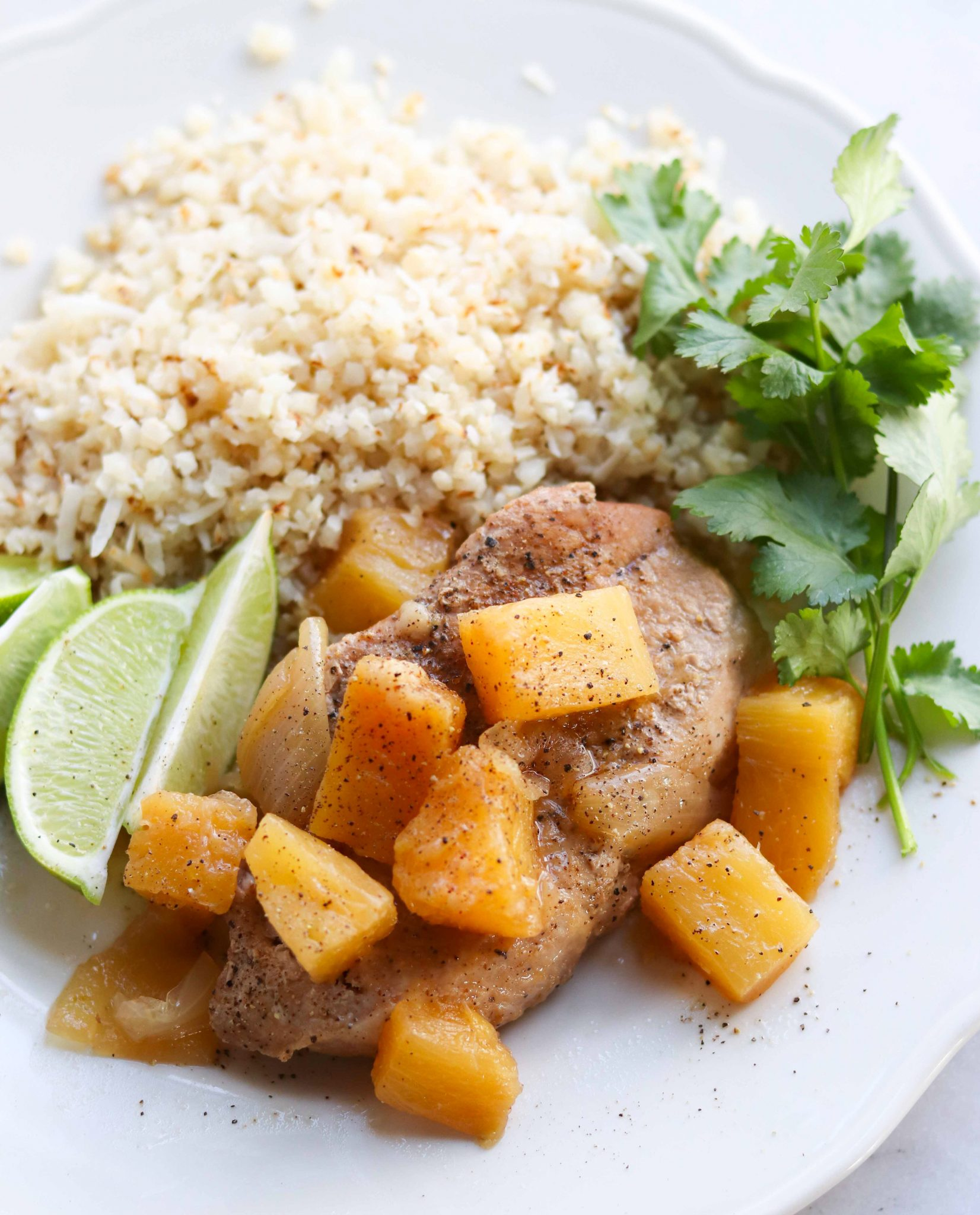 Easy Instant Pot Pineapple Pork Chops served with Cauliflower Rice, lime slices, and cilantro.