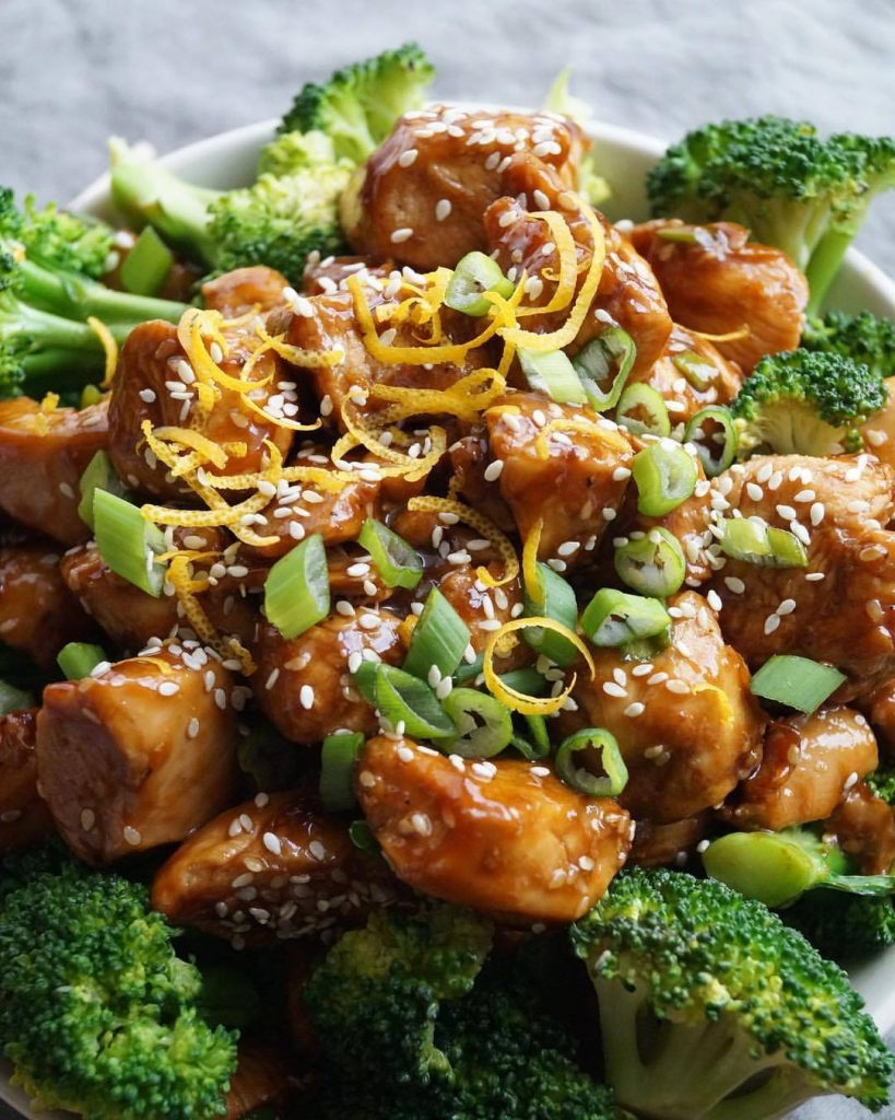 Orange Sesame Chicken and Broccoli, topped with sesame seeds and orange zest.