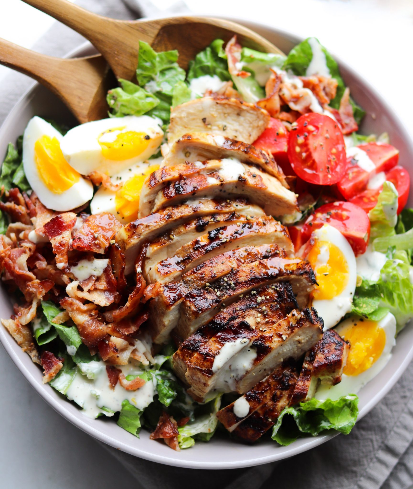 A large gray bowl is filled with chopped romaine lettuce, quartered hard boiled eggs, crispy crumbled bacon, and a sliced grilled chicken breast. The creamy caesar dressing is drizzled on top.