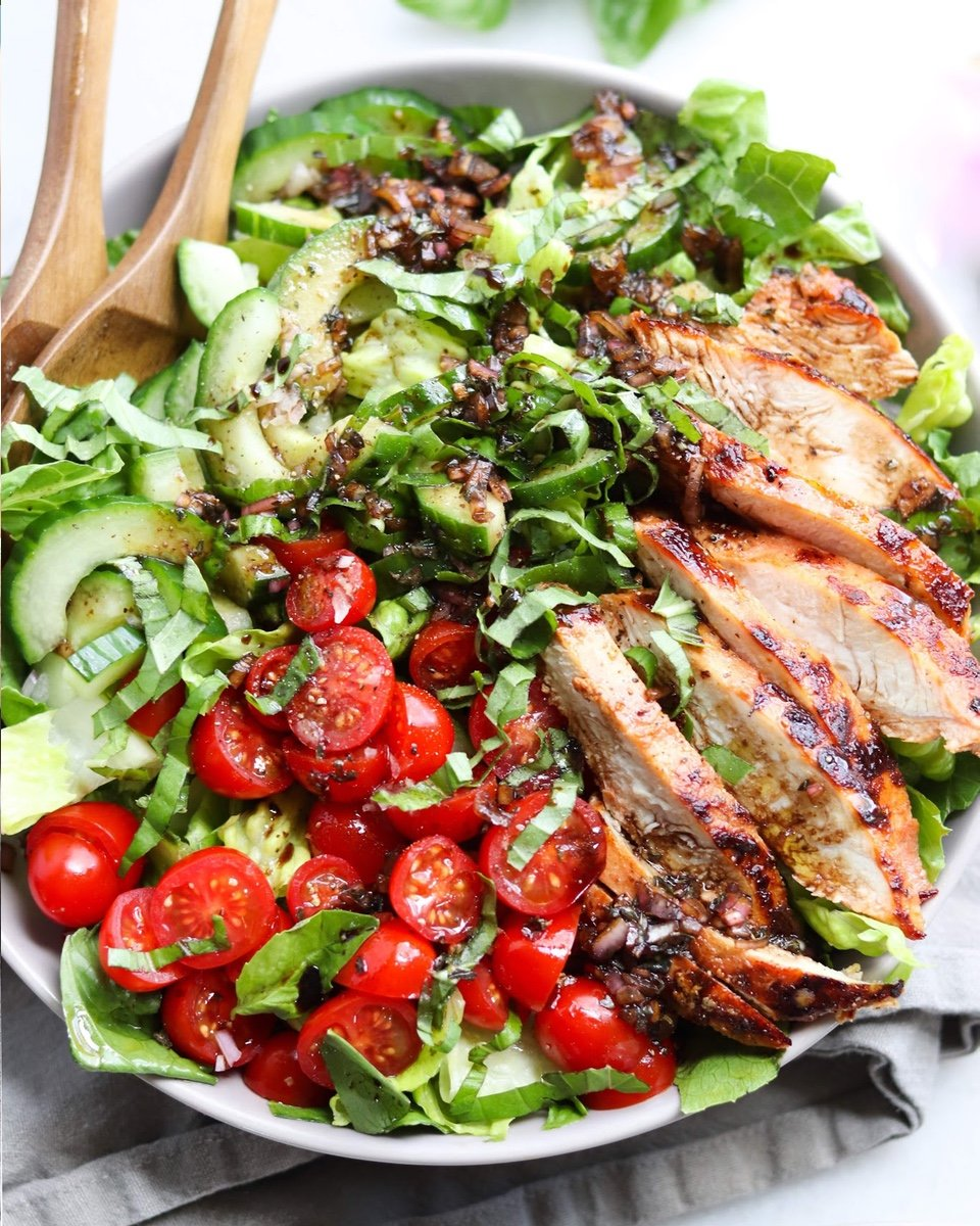 A close up of the finished dish. The marinated tomato basil turkey cutlets have been grilled to perfection and sliced, laid out on the chopped romaine. The sliced tomatoes and cucumbers are also on top of the salad and the dressing has been drizzled on top. The whole salad is topped with cracked black pepper and torn basil leaves.