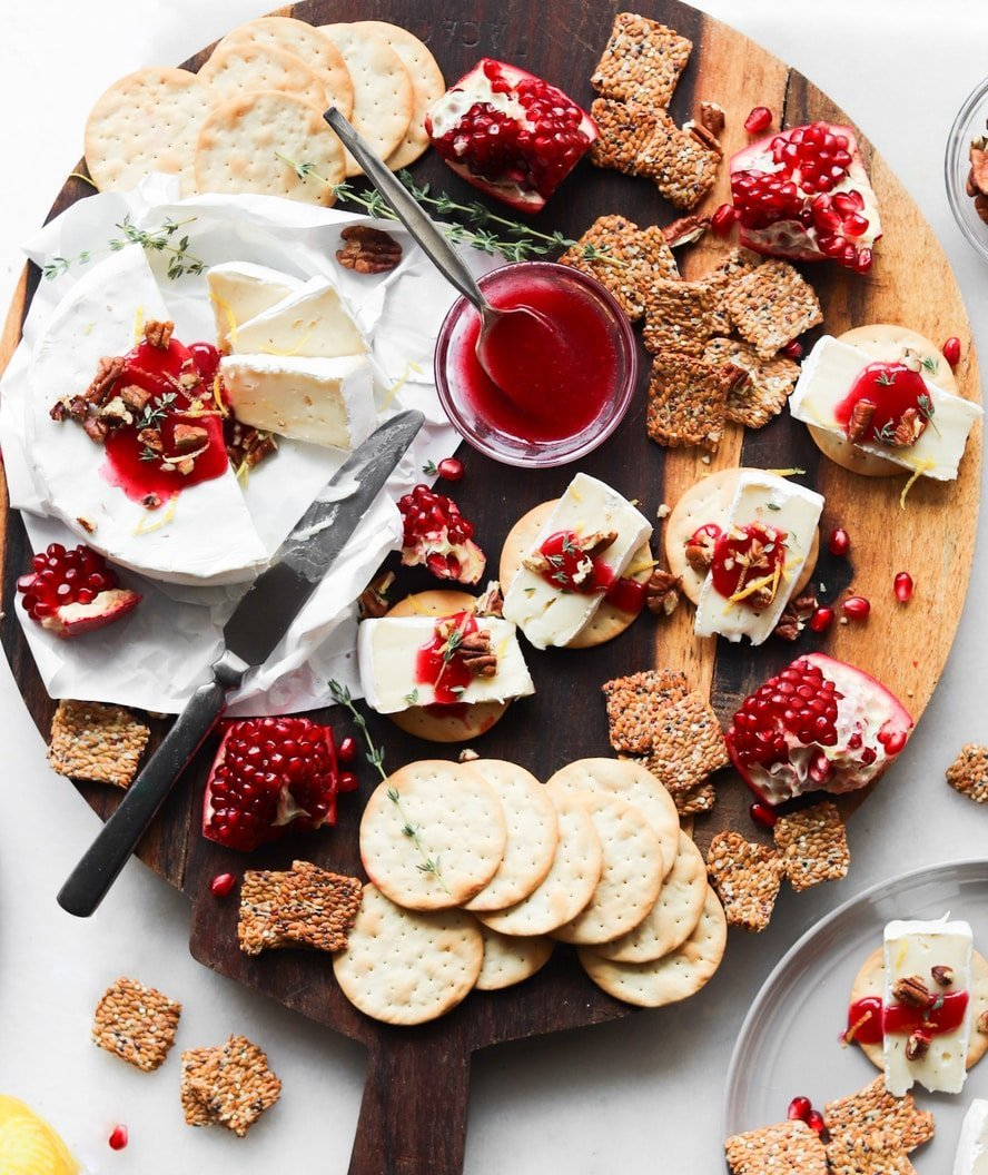 A wooden cheeseboard laid on a white marble board, topped with assembled crackers, brie cheese, cranberry horseradish sauce, and crumbled pecans, surrounded by pomegranate segments and extra crackers.