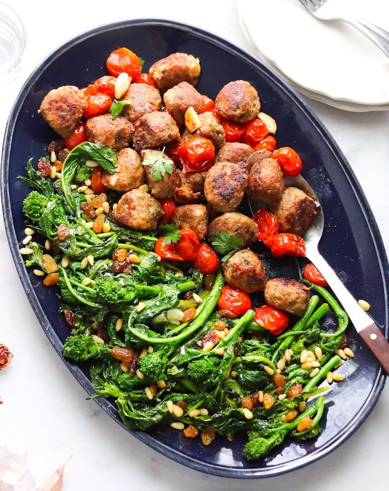 A long blue serving tray filled with meatballs, burst cherry tomatoes and broccoli rabe.