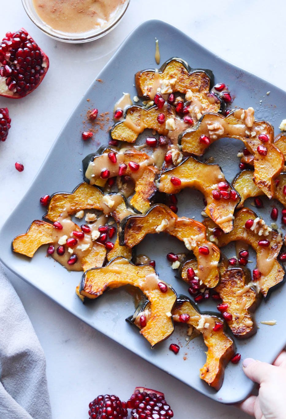 Sliced, Roasted butternut squash is plated on a blue square dish and drizzled with maple tahini drizzle and sprinkled with pomegranate arils.