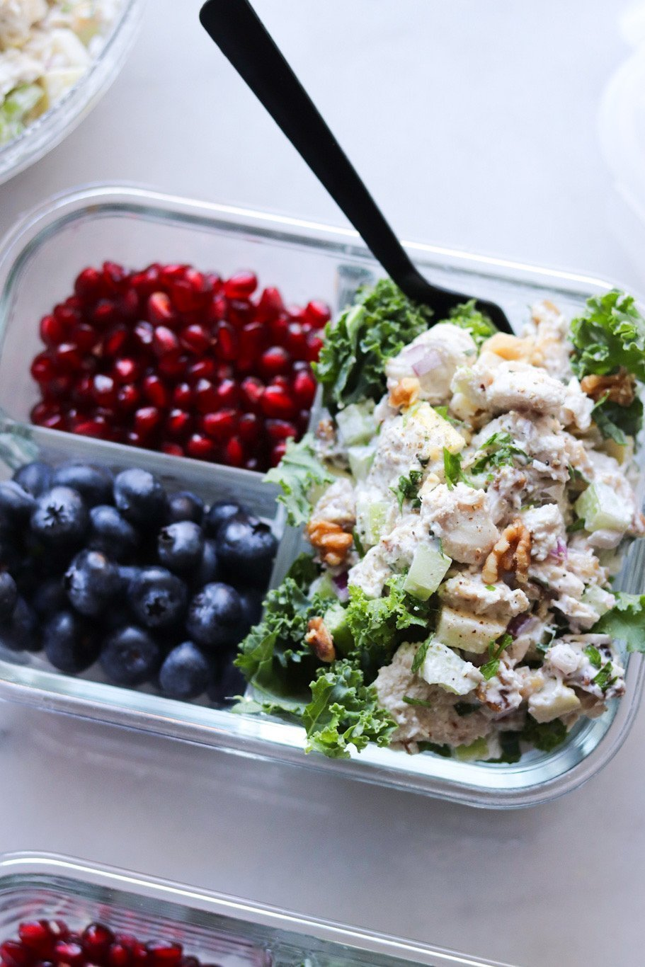 A glass meal prep container is filled with the apple walnut chicken salad, fresh kale, and pomegranate and blueberries.