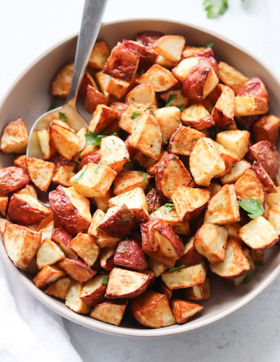 A gray bowl with crispy air fryer roasted potatoes and a large serving spoon.