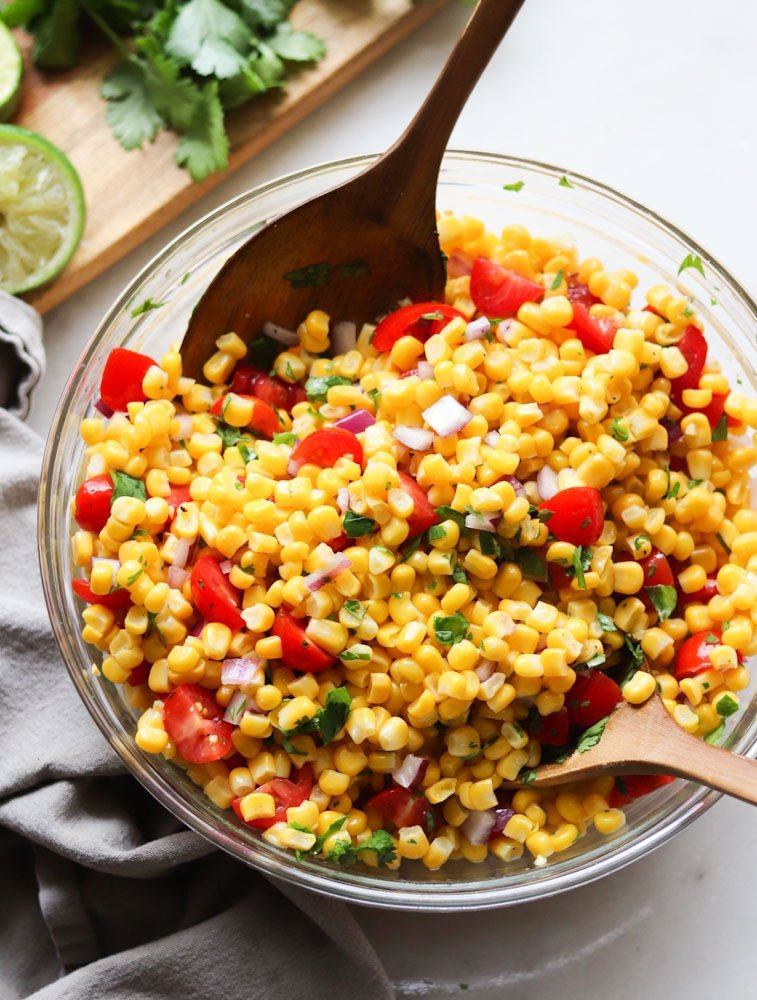 Chipotle Copycat Corn Salsa mixed in a large glass bowl with two wooden serving spoons.