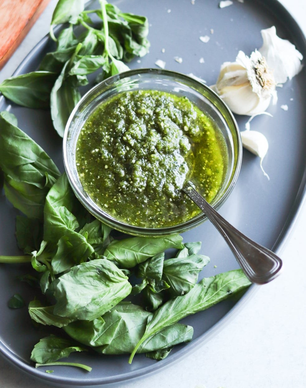 A glass dish with dairy free, Whole30 pesto inside surrounded by basil and garlic.