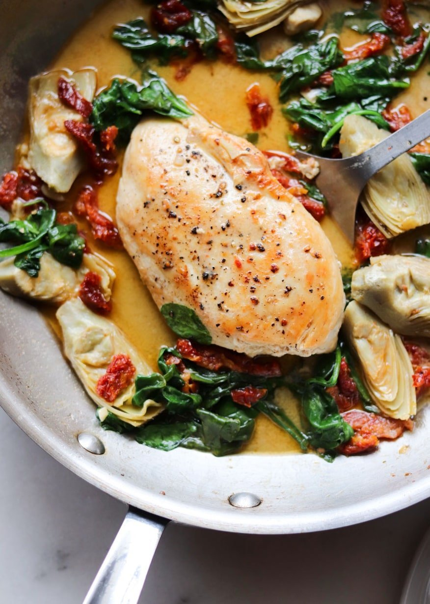 Close up of cooked chicken breast in a creamy sauce with spinach, artichokes, and sundried tomatoes in a skillet