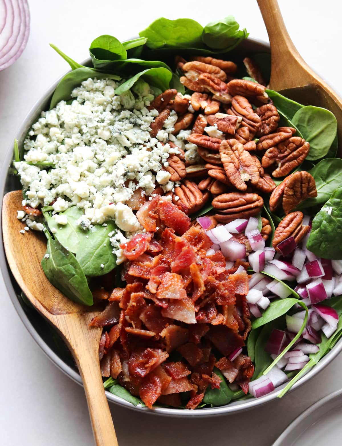A gray bowl filled with spinach, crumbled bacon, onion, pecans, and blue cheese with two wooden serving forks.