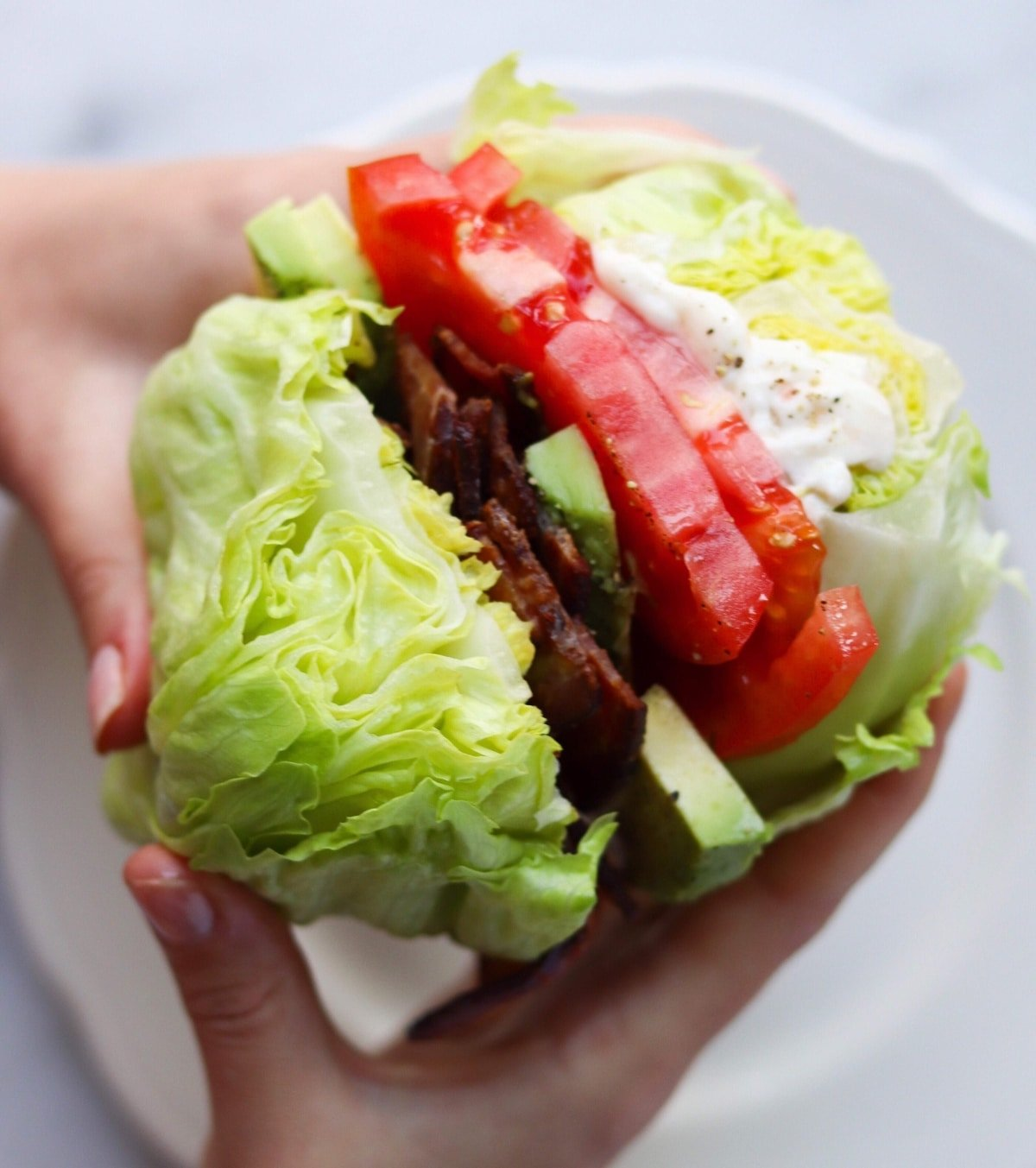 Two hands holding the finished Wedge Salad Sandwich over a white plate.