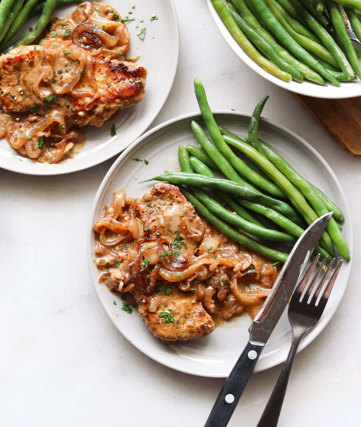 Cook pork chop on a gray plate, serve with green beans.